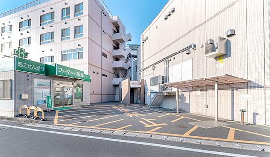 写真: 駐車場病院裏側「ファーマシィ薬局」前